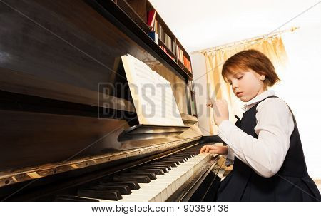 Concentrated small girl in uniform playing piano