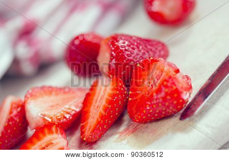 Fresh strawberries on a wooden board and knife