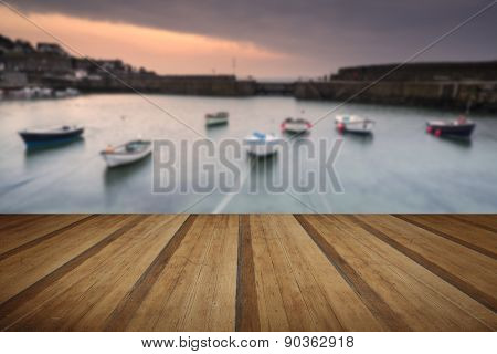 A traditional Cornish fishing village before sunrise with wooden foreground
