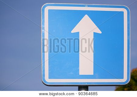 One-way traffic sign against blue sky