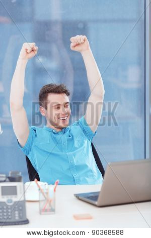 Businessman sitting with arms above his head