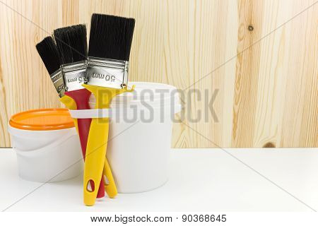 Brushes With Can Of Paint Against Wooden Background