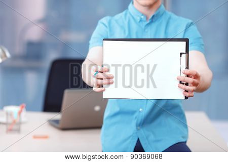 Businessman sitting on desk holding  folder with papers