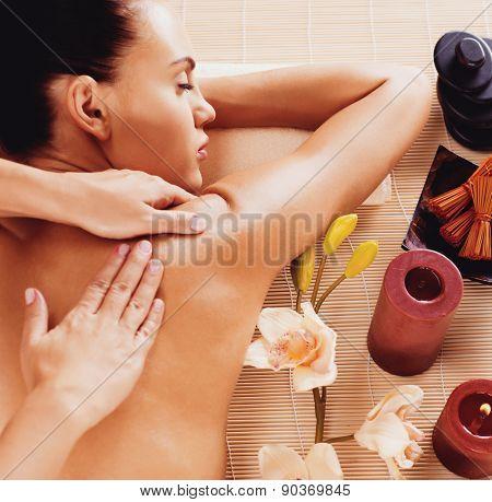Adult woman in spa salon having body relaxing massage.
