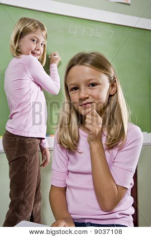Girls Writing On Blackboard In Classroom