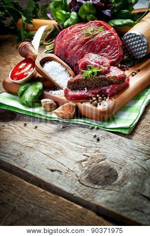 Raw meat on wooden cutting board with herbs