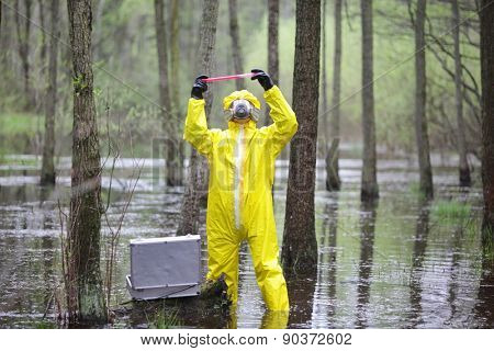 professional in protective coveralls with mini lab in contaminated environment