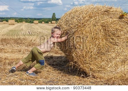 Boy Pushes Bale Of Straw