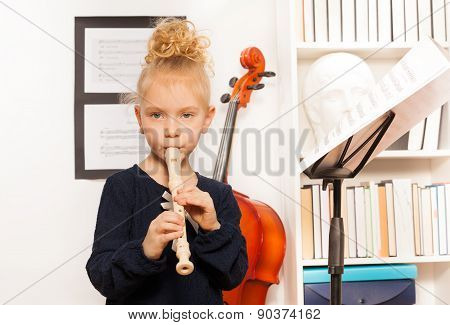 Blond curly girl plays flute standing near cello