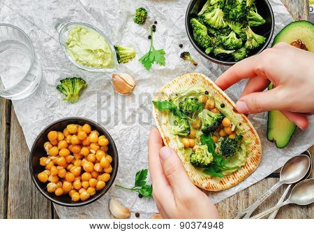 Man Holding Tortilla With Roasted Broccoli And Chickpeas And Avocado Sauce