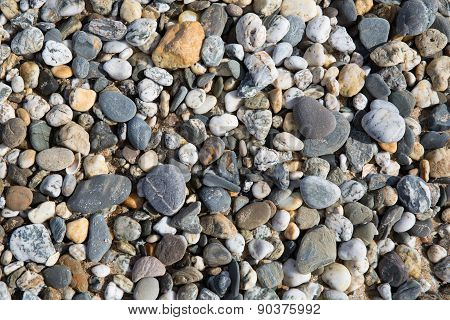 Pebble background texture with many pebbles of different sizes and shapes from Fistral beach Newquay