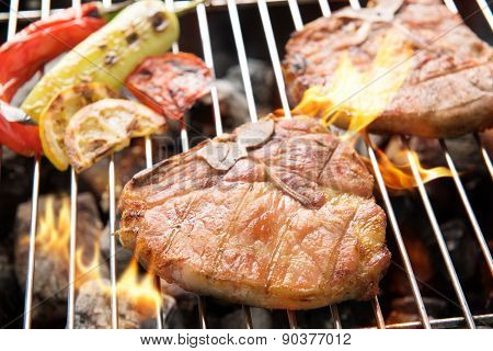 Grilled Pork Chop And Vegetables On The Flaming Grill