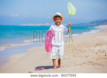 Kid boy walking the tropical beach