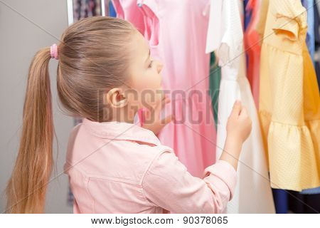 Small girl choosing colorful dresses in a store