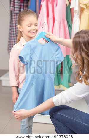 Young mother tying on the dress her small daughter