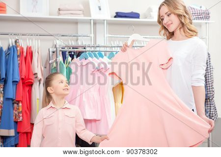 Mother showing a pastel pink dress to her small daughter