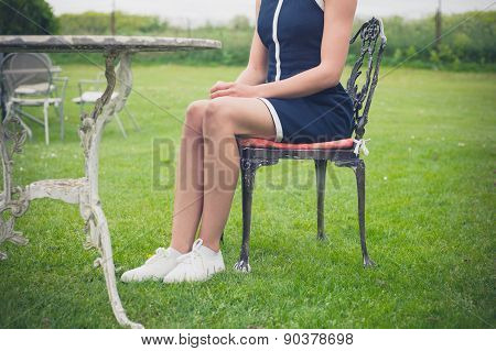 Woman Relaxing On Chair In A Garden