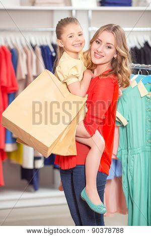 Happy mother with her daughter and lots of new purchases in pack