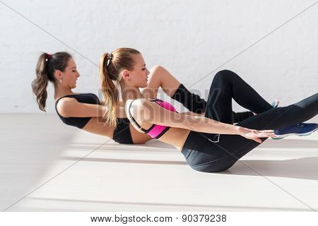 Two sporty women doing exercise abdominal crunches, pumping a press on floor in gym concept training