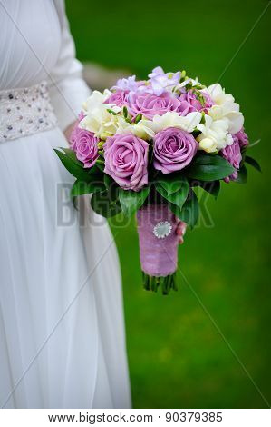 Bridal Bouquet Of Purple Roses In Bride's Hands