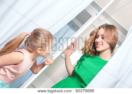 Small girl looking at her mother inside a fitting room