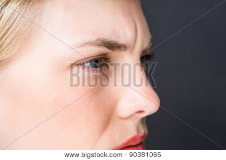 Nervous blonde woman on black background