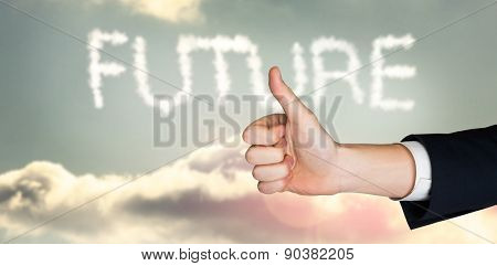 Hand showing thumbs up against clouds spelling out future