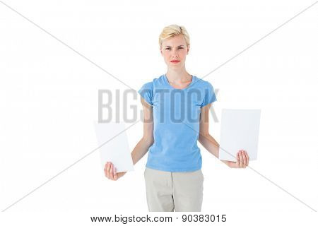 Stern blonde woman holding sheets of paper on white background