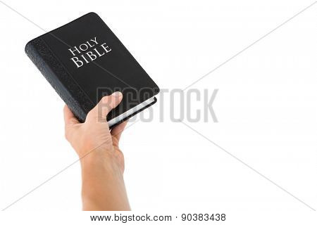 Hand holding bible on white background
