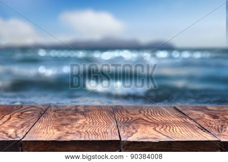 Empty wooden table with blurred sea on background, natural background with bokeh