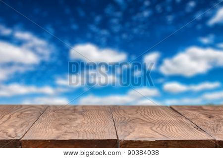 Empty wooden table with blurred sky and clouds on background, natural background with bokeh