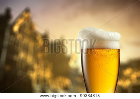 Glass of beer against blurred european city with beautiful lights on background at evening