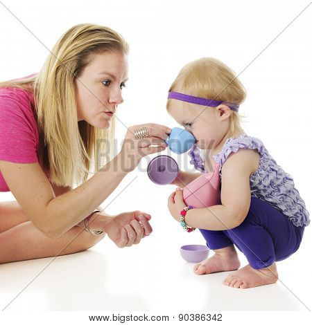 Mother and daughter playing tea party.  Mommy holds the toy tea cup to her squatting daughter's mouth.  On a white background.