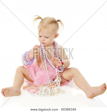 An adorable 2-year-old draped in beaded necklaces while looking at other twisted around her writs.  On a white background.