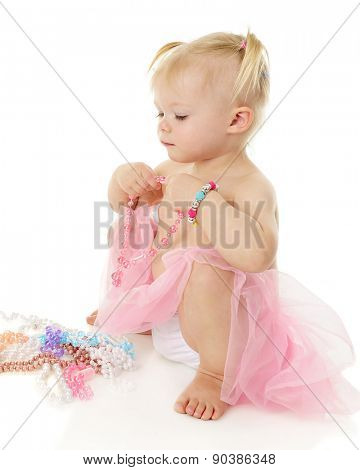 A beautiful baby girl holding and admiring multiple beaded necklaces. On a white background with plenty of space above the necklaces for your text..