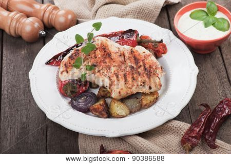 Grilled chicken steak with roasted potato and vegetables on wooden table