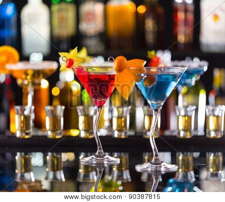 Martini drinks served on bar counter with blur bottles on background