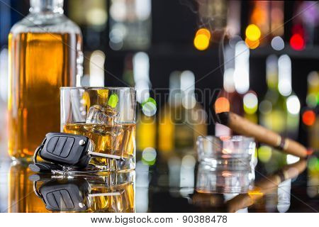 Whiskey drink with smoking cigar and car key on bar counter. Concept of alcohol danger and car driving