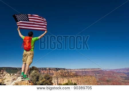 Man's back with rucksack, USA flag, Grand Canyon