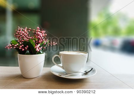 Coffee Cup And Flower On Wooden Table In Coffee Shop