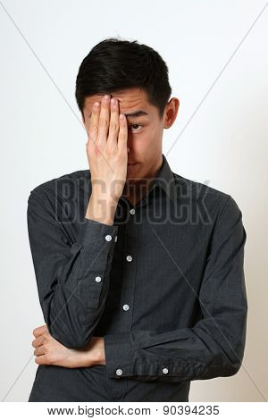 Frustrated young Asian man covering his face with a palm.