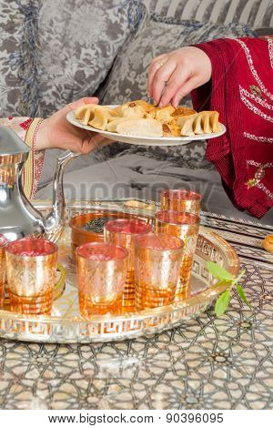 Hands of a moroccan woman presenting ramadan cookies and tea to a guest