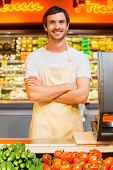 stock photo of cashiers  - Handsome young male cashier keeping arms crossed and smiling while standing at supermarket checkout - JPG