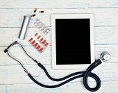 stock photo of medical supplies  - Medical tablet with medical supplies on wooden background - JPG