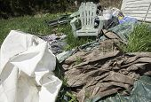 picture of tarp  - Garbage in back yard of house in grass - JPG