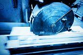 stock photo of sawing  - Big metal saw at work in workshop - JPG