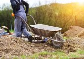stock photo of wheelbarrow  - Unrecognizable bricklayer with an empty wheelbarrow walking - JPG
