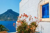 stock photo of greek-island  - Typical blue wooden Greek window and red flowers againt white - JPG