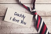 stock photo of daddy  - Daddy I love you sign on paper and colorful tie laid on wooden floor backround - JPG