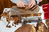 foto of tobacco leaf  - Man processing the tobacco leaves and making cigars with simple tools